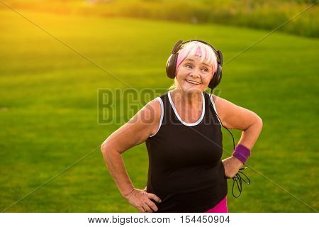 Old lady in headphones. Smiling woman on outdoor background. Day starts with good music. All of my favorite hits.