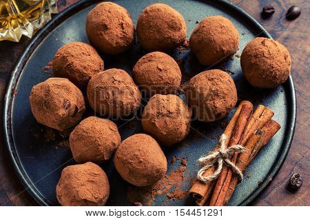 Dark chocolate truffles on plate and group of cinnamon sticks aside