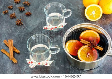 Stainless steel pot with hot freshly prepared homemade mulled wine two mulled wine glasses cinnamon sticks star anise and oranges on black marbled kitchen worktop.