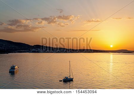 Sunset on the sea. The sun on a bright orange pillow leaving of the day which throwing last rays on the air clouds. In the distance a mountain coast. A yacht and a sailer in the foreground in complete calm.