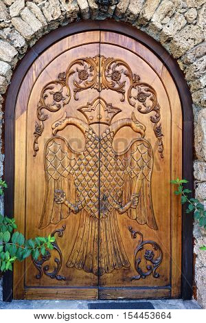 Medieval wooden door with byzantine eagle in Kastraki village Meteora Greece