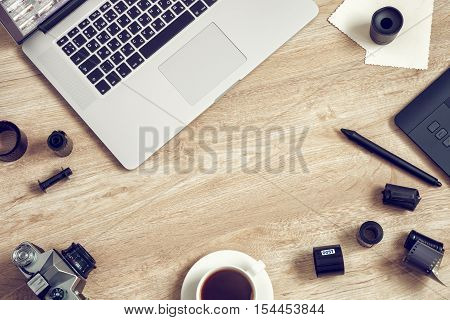 Work space for freelancer photographer retoucher designer: laptop retro camera film rolls digital tablet and coffee cup. Retro toned photo.