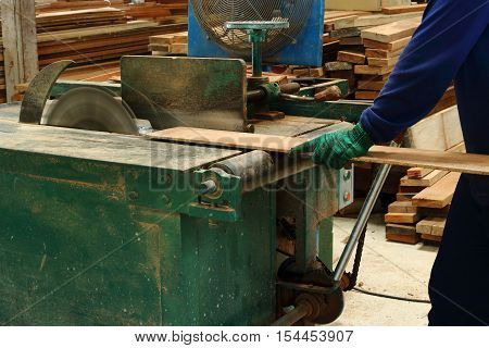 Carpenter sawing a piece of wood on a table saw