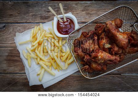 deep fried chicken wings on fryer with bbq sauce for dip