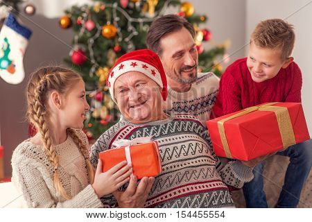 Happy old man is receiving Christmas gifts from his grandchildren and son. He is holding boxes and smiling. Family is sitting together on couch at home