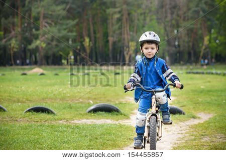 Happy Cute Blond Kid Boy Having Fun His First Bike On Sunny Summer Day