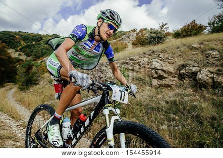 Privetnoye Russia - September 22 2016: closeup of rider mountainbiker rides on a mountain trail during Crimean race mountainbike