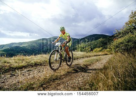 Privetnoye Russia - September 22 2016: woman rider cyclist riding uphill on a background of mountains and clouds during Crimean race mountainbike