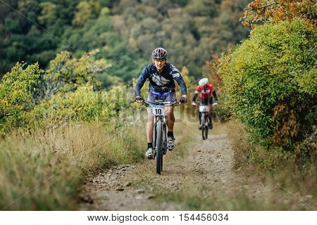Privetnoye Russia - September 22 2016: middle-aged man racer cyclist riding uphill during Crimean race mountainbike