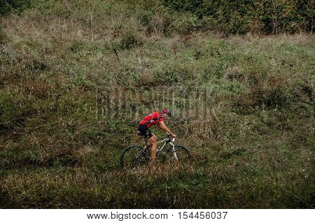 Privetnoye Russia - September 22 2016: racer mountainbiker rides on mountain in grass during Crimean race mountainbike