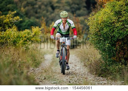 Privetnoye Russia - September 22 2016: male rider cyclist riding uphill on a mountain trail with smile on face during Crimean race mountainbike