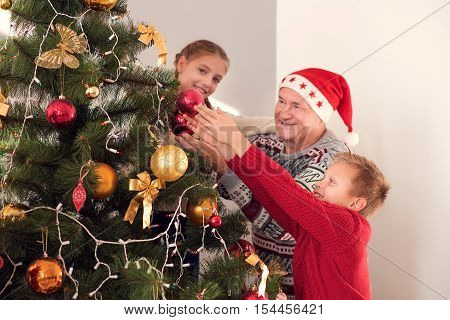 Lets prepare for New Year together. Happy old man is beautifying fir-tree with his grandchildren. They are holding toys and smiling