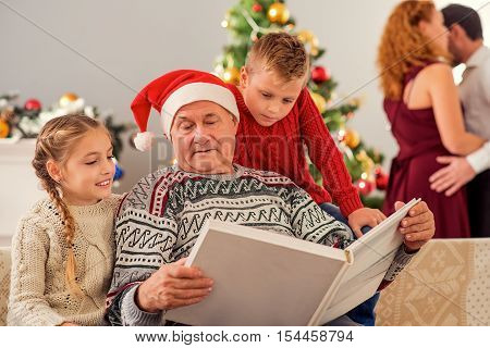 Old grandfather is showing album of photographs to his grandchildren. Boy and girl is sitting on couch and smiling. Their parents are dancing near Christmas tree