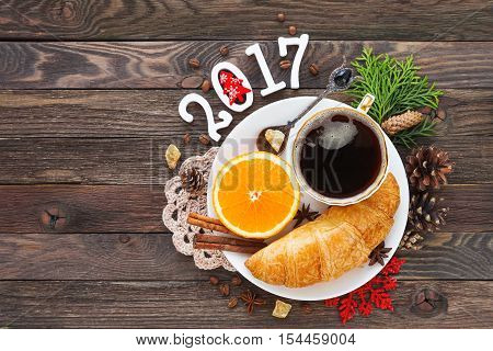 Christmas and New Year 2017 background with continental breakfast - cup of hot coffee with cinnamon fresh orange and croissant. Decorations - snowflake crochet napkin pine cones.