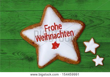 Frohe Weihnachten (in German Merry Christmas) Cinnamon Star On Green Wood Background