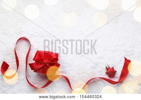 Christmas red gift with ribbon on snow