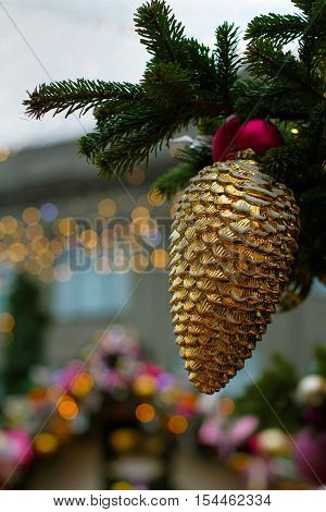 Christmas toy bump hanging on tree branch on the background of golden lights.