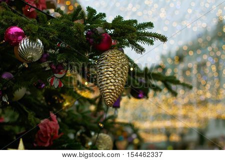 Christmas toy bump and balls hanging on tree branch on the background of golden lights