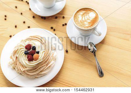 break time, beautiful latte macchiato and a dessert on a wood desk