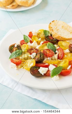Summer heirloom tomato salad with fresh feta cheese on white plate on blue background selective focus vertical
