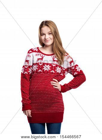 Teenage girl in jeans and long red winter sweater with nordic pattern. Young woman posing, arm on hip. Studio shot on white background, isolated.