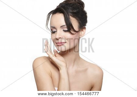 Young smiling beautiful girl applying cream on her cheek