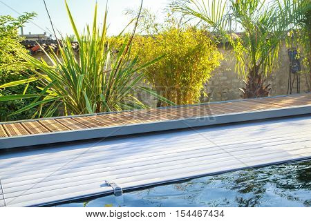 closeup on swimming pool roller-shutter covers in private pool