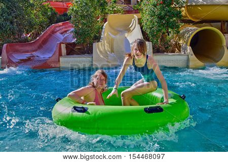 Happy mother and her daughter enjoy water slides in Aqua Park