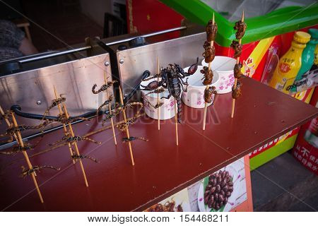 ZHUJIAJIAO CHINA - AUGUST 30 2016: Scorpions insects and bugs on spits are offered to shopping tourists as food by a vendor in the market street stall in Zhujiajiao China on August 30 2016.