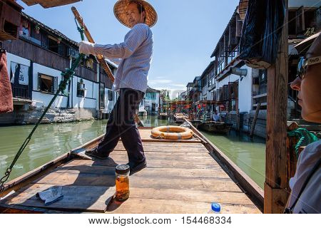 ZHUJIAJIAO CHINA - AUGUST 30 2016: Boatman transports tourists by Chinese gondola on canal of ancient water town with a history of more than 1700 years in Zhujiajiao China on August 30 2016.