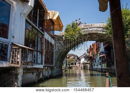 ZHUJIAJIAO CHINA - AUGUST 30 2016: Tourists see the sights of ancient water town with a history of more than 1700 years from top of bridge over canal in Zhujiajiao China on August 30 2016.