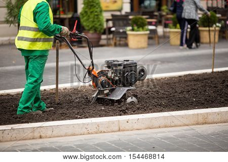 Man working in the city streets with Garden Tiller. Close-up male plow. Cultivator machine