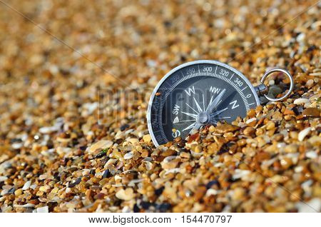 Metal compass in the sand on the seashore. Navigation equipment.