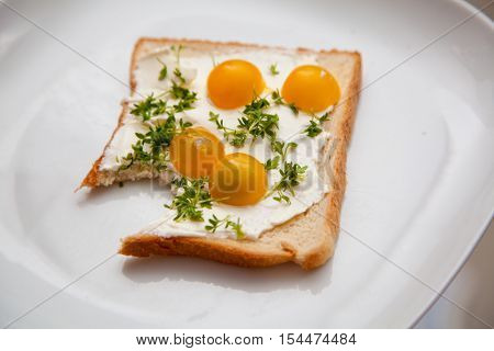 toast with cream cheese yellow tomatoes and cress with piece bite off.