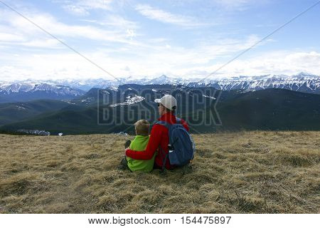 Father and son enjoying the view from top of Jumpingpound mountain,Alberta, Canada.