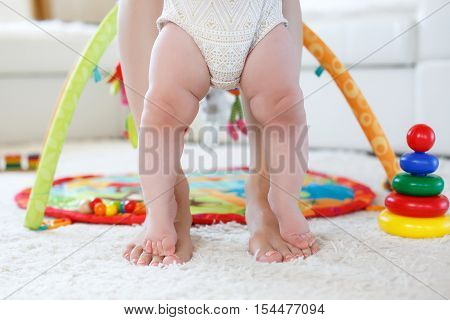 Bare pink feet of a little girl of 8 months standing on my mother's bare feet with a pedicure pink color,the girl dressed in panties white with light brown pattern,mom's legs standing on white soft rug in the nursery on the background of toys