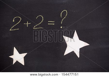 math symbols on a black background. question mark for the math task on the board. hand drawn question mark on chalkboard with stars. Education back to school concept
