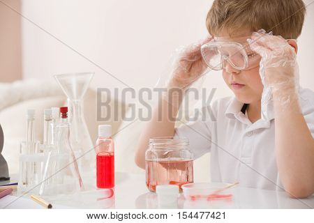 Cute kid boy in glasses making science experiments. Little child working with liquids.