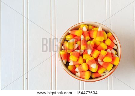 A bowl of candy corn on a wooden table.