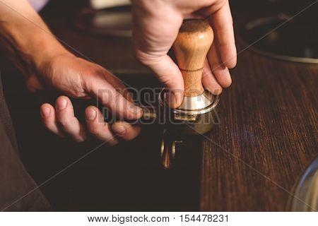 man at coffeeshop preparing coffee grinder indoors, close up