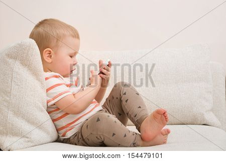 Adorable toddler boy sitting on the sofa in the living room and playing with smartphone. Child learning how to use smartphone. Boy texting on the phone. - technology and lifestyle concept.