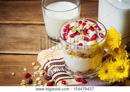 Healthy breakfast with yogurt, muesli and pomegranate seeds in glass on wooden background. Concept for healthy nutrition.
