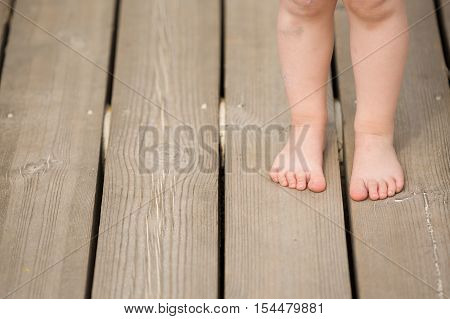 Closeup of child's bare feet on wooden floor. Toddler's legs and foot.