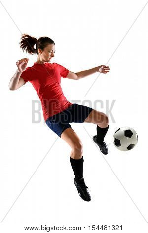 Portrait of female soccer player kicking ball isolated over white background