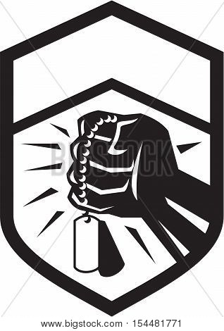 Illustration of a clenched fist clutching holding dogtag set inside shield crest done in black and white retro style.