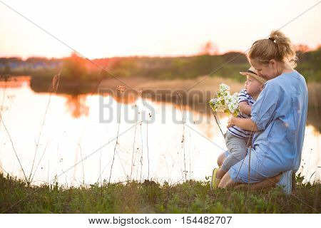 Young beautiful mother hugging her little toddler son on a sunset in a wild flowers field near lake. Happy woman with her baby boy on a summer sunny day. Family walking by the river. Lifestyle concept
