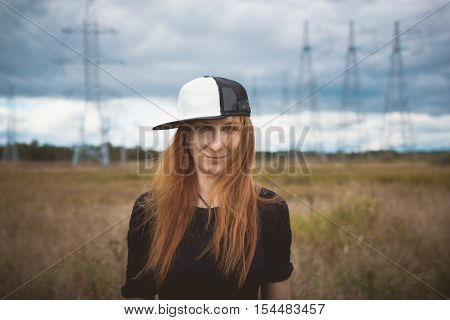 Young energy happy woman in hip-hop cap on yellow field with power pylons, close up, cloudy autumn