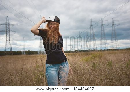 Young energy happy woman wears a cap hip-hop on yellow field with power pylons, wide angle, cloudy autumn