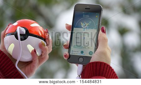 Samara, Russia - November 1, 2016: woman playing pokemon go on his iphone. pokemon go multiplayer game with elements of augmented reality. Catching the Vaporeon pokemon.