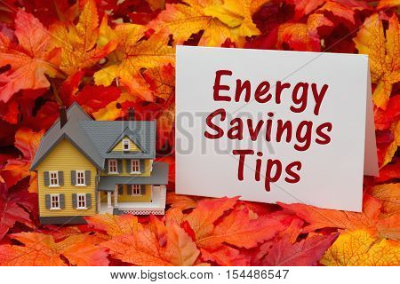 Home energy savings tips in the fall season Some fall leaves and yellow and gray house and greeting card with text Energy Savings Tips